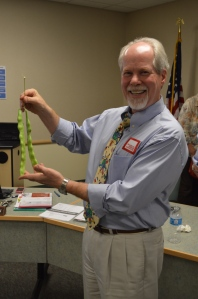 Dr. Hewins shows of giant beans from the district garden