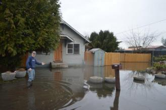 Kevin Kennedy wades through his front yard to watch the county crew's progress
